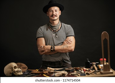 Moustached craftsman with creative capon his head on, posing near his working place, at the table with crafting tools and rough leather in studio. Small Business, Cobblering, Leather Workcraft