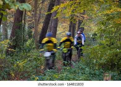 Moutain bikers, cyclist, speeding in beautifully colored autumn wood, unrecognizable by motion blur