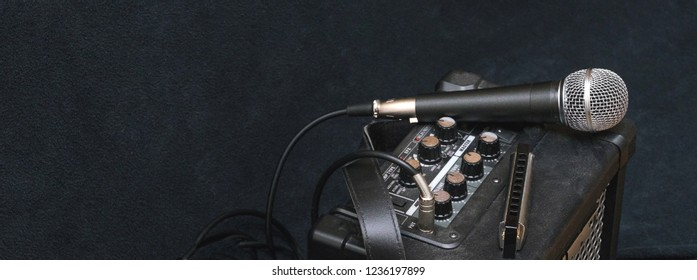 mouth blues diatonic harmonica - playing blues with  microphone and amplifier on a black background, banner concept