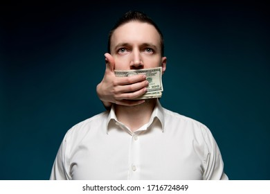 The mouth of a business man in a white shirt is covered with money. Buying silence for dollars