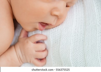 The mouth and the hand of a newborn baby.