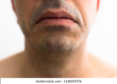 mouth of a man with a shaved beard. detail of the lips with sad expression, the foreground with blurred white background. lower part of a white man's face