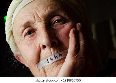 The mouth of the old grandmother is sealed. Violation of an individual's rights. Silence. Fear. Forced silence. Silence. Help me. Help concept. Ask for help. Need protection. Granny is under pressure.