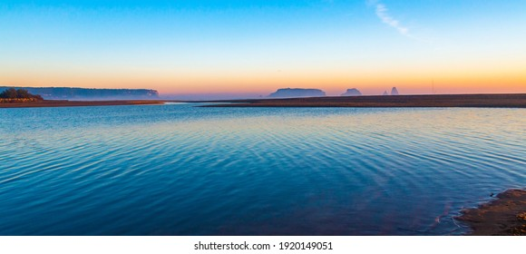 Mouth of the river Ter in the Mediterranean Sea with the Medes Islands and Estartit in the background. Panoramic sunrise landscape with the river flowing calmly. Morning lights with calm atmosphere.