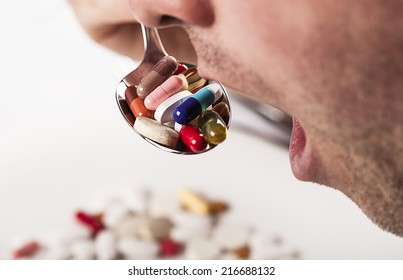 mouth with spoon full of pills nutrition eating concept