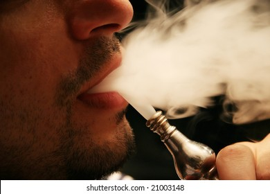 """The mouth of a Syrian man smoking the traditional hubble-bubble (""""or hookah"""")."""