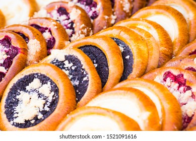 Mouth watering sweet round cakes (Czech: kolace) with cream cheese, poppy seed, plums, strawberries or forest fruit filling.  Closeup image of tasty bakery products on traditional autumn market stand.
