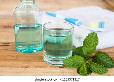mouthwash from herbal peppermint with toothbrush terry cloth for health care oral cavity with peppermint leaf on background wooden