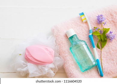 mouthwash and toothbrush for healthy care oral cavity with soap from herbal and bath towel for body skin care prepare bathing on background white wood