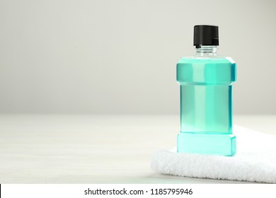 Mouthwash with towel and space for text on light background. Teeth hygiene