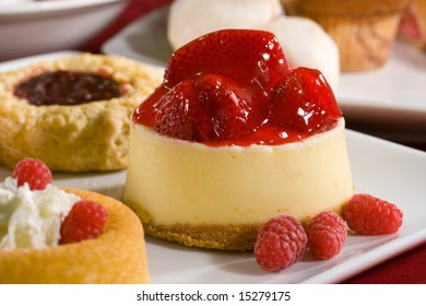 Mouthwatering cheesecake with strawberries on top, raspberry thumbprint scone, raspberry shortcake and fresh raspberries make up this shot.