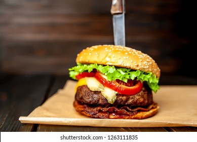 mouth-watering, delicious homemade burger used to chop beef. on the wooden table. The burgers are inserted knives