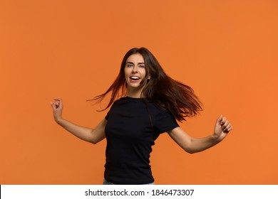 Move energetically. Positive beautiful caucasian woman in black t-shirt dances with arms outstretched, feels carefree and upbeat, extremly happy and expresses joy. Isolated over orange background