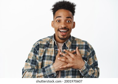 Moved and touched african american guy being grateful, smiling amazed and happy, holding hands on heart, say thank you, feeling pleasure, standing against white background