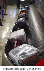 The movement of baggage on a conveyor belt.