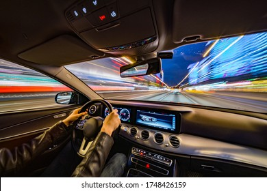 Movement of the car at night at high speed view from the interior with driver hands on wheel. Concept spped of life.