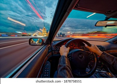 Movement of the car at night at high speed view from the interior with driver hands on wheel. Concept spped of life. Long exposure photo.