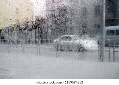 The movement of cars on the road in rain. Drops of rain outside the busy street.