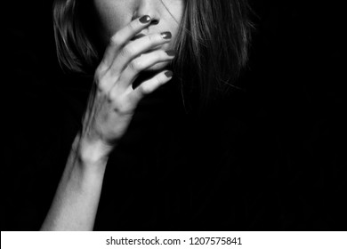 movement concept. Closeup portrait of young woman hiding face with hand, isolated on black background. Human emotion, expression, rights & communication. Text space. Monochrome studio shot