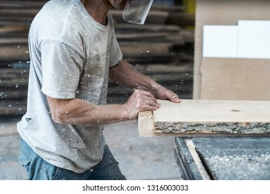 Movement cropped profile side view photo of cabinetmaker or mature handyman in protective mask push wood plank board on table saw make furniture in workroom