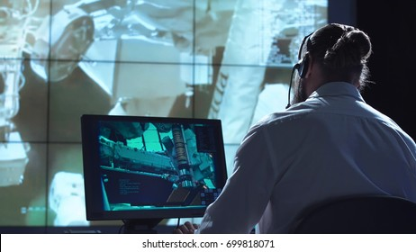 Movement shot back view of man working on space mission in control center. Elements of this image furnished by NASA.