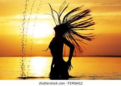 Movement of wet hair of bathing girl against sea sunset
