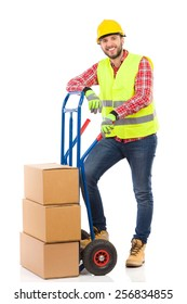 Mover in reflective clothes. Relaxed manual worker lean on the push cart. Full length studio shot isolated on white.