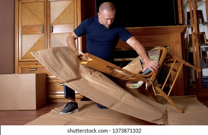 mover wrapping cheer and packing boxes. professional moving company