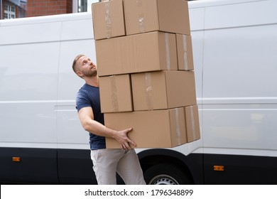 Movers Carrying Heavy Large Box Stack Near Truck