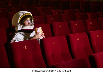 A movie astronaut looks at a movie while eating pop corn and enjoying the movie. Concept of: cinema and space films, film of the other world, surreal situations.