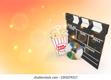 Movie clapper board, box of popcorn and a DVD disc isolated on white
