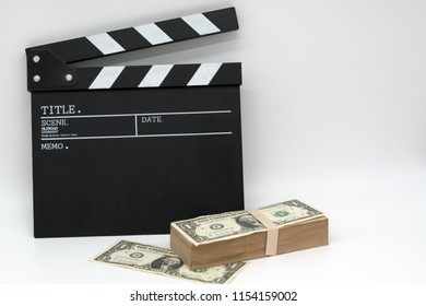 Movie clapper board and money on a white background,Movie business.