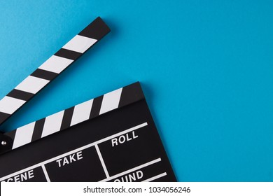 Movie clapper board on blue background with copy space, close-up, view from above. Cinema and movie time concept