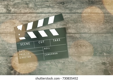 Movie clapper board on wooden background with bokeh lights.