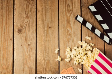 Movie clapper board and popcorn on wooden background. Top view from above