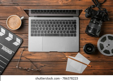 Movie clapper, laptop and camera on wooden background, top view