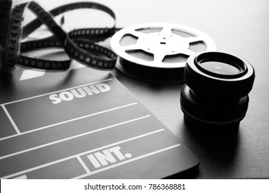 Movie clapper and lens on grey background, closeup
