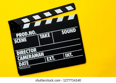 Movie clapper on a yellow background with copy space. Flat lay.