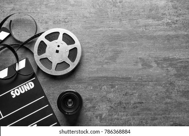 Movie clapper and reel on grey background, top view
