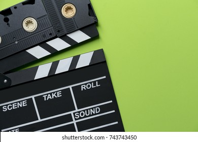 movie clapper and video cassette tapes on green background; film, cinema and video photography concept