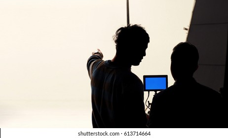 Movie director and photographer are talking or consulting to making studio set before shooting video and silhouette background lighting.