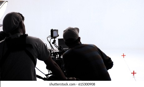 Movie director and photographer are talking or consulting to making studio set before shooting video production and silhouette background lighting.