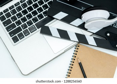 Movie maker with movie editing device,laptop, earphone, movie clapper board, note pad on white background.