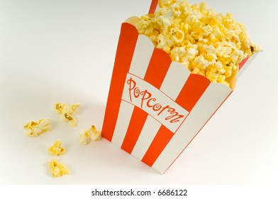 Movie popcorn on white background with red striped box and freshly popped popcorn on white background