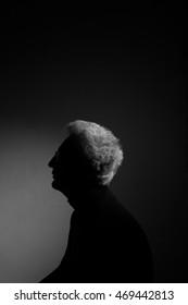 Movie poster, film noir concept. Profile portrait of fashionable mature man wearing trendy eyewear, black turtleneck. Silver hair. German expressionism style. Contrastive monochrome studio shot