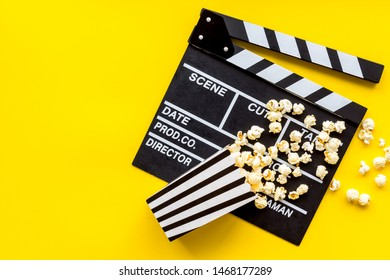 Movie premiere concept with clapperboard, popcorn on yellow background top view space for text