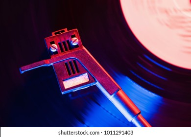 Movie of retro-styled record player spinning vinyl black record. Cinemagraph. Top view. Beautiful neon night colors.