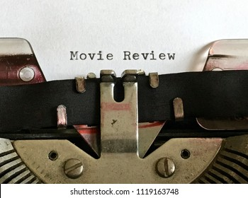 Movie Review, heading title typewritten on white paper in black ink on vintage manual typewriter machine