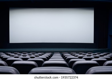 Movie theater with black seats and large blank screen. Concept of empty cinema hall.