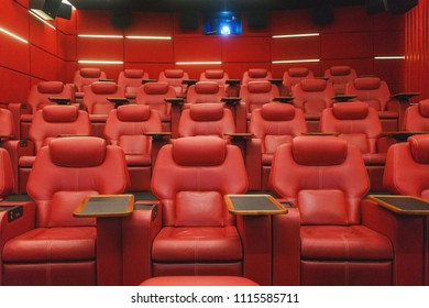 Movie theater empty auditorium with red leather comfortable chair with a table. Shooting in difficult conditions with high sensitivity and noise.